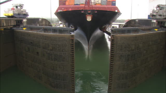 Stone gates open to reveal the hull of a huge ship.