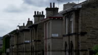 Stone terraced houses line a street in Saltaire, England. Available in HD.