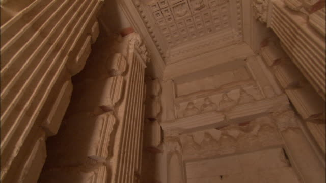 A stone tomb is decorated with columns and carvings in the ancient city of Palmyra. Available in HD