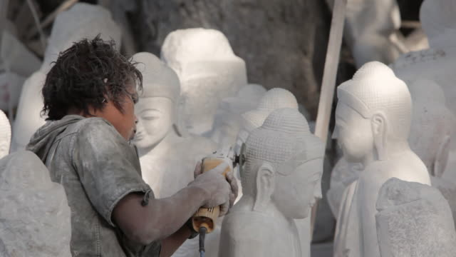 MS A stonemason carves a marble Buddha statue in Mandalay's stone carving district / Mandalay, Myanmar