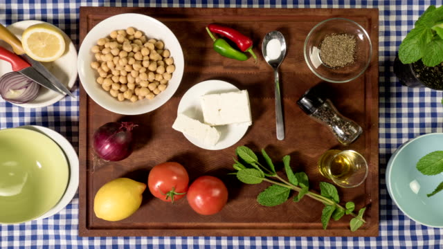 Stop motion: making chickpea salad with feta onion tomatoes herbs