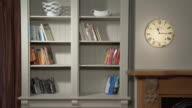 MS T/L Stop motion of books arranging in bookshelf, time changing clock on wall / Auckland, North Island, New Zealand