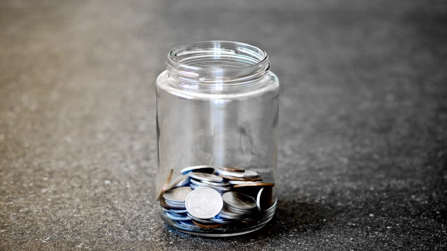 Stop motion of glass jar filled with coins