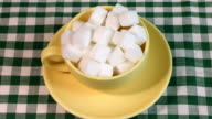 Stop motion of sugar cubes being added to a cup
