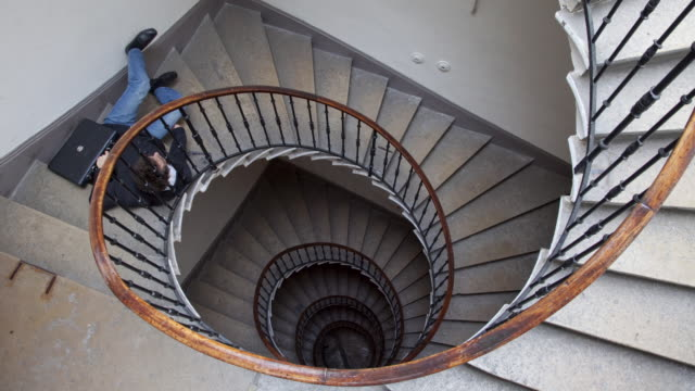 Stop Motion / Pixilation shot of young businessman falling in stairs of an apartment building