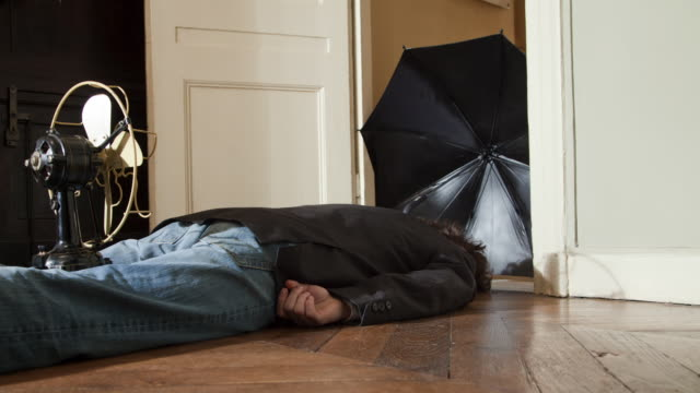 Stop Motion / Pixilation shot of young man slipping on floor while pulled by umbrella and fan in apartment