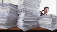 Stop Motion shot of businessman suddenly hidden by piles of paper