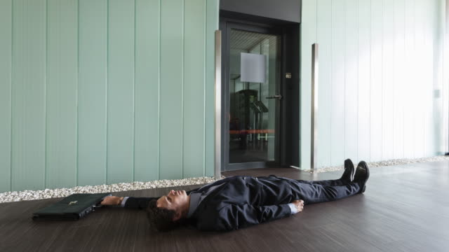 Stop motion shot of unconscious Businessman sliding on floor pulled by his wallet