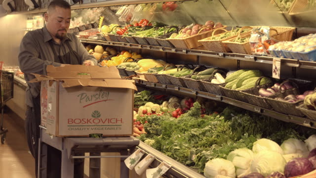 MS store employee filling shelves in produce section with fresh bunches of raddishes