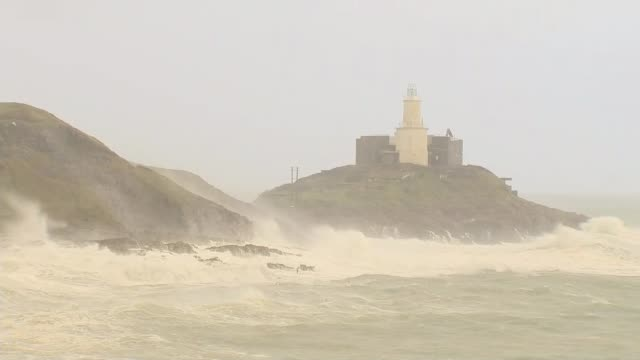 Storm Brian batters parts of the UK WALES Swansea Bay Various shots waves crashing on coast during Storm Brian and people watching