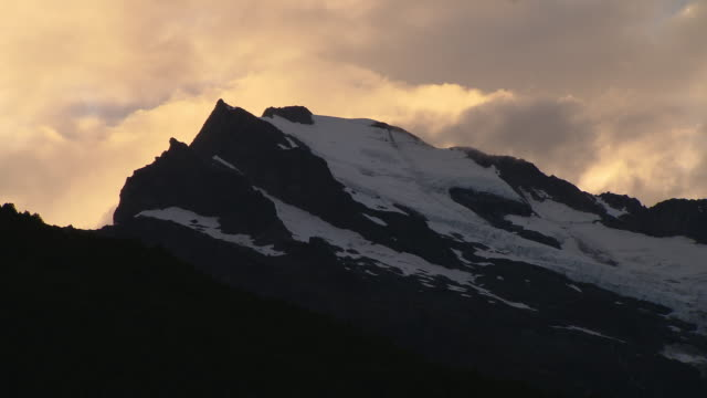 Storm clouds drift over a snowy ridge as night falls.