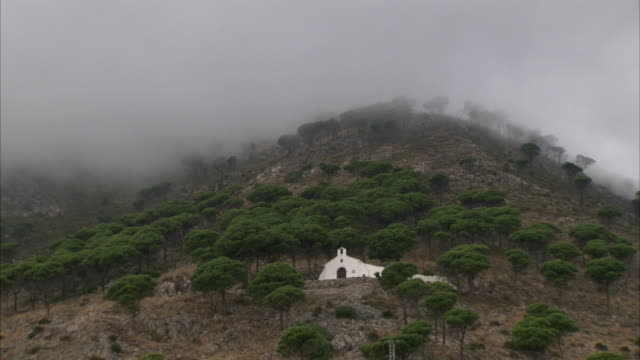 Storm clouds hang over a church on a mountainside near Mijas, Spain.
