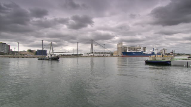 Storm clouds loom over a harbor where a variety of ships float.