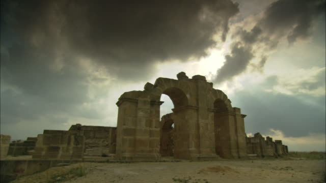 Storm clouds loom over an archway at Uthina Amphitheater in Tunisia.