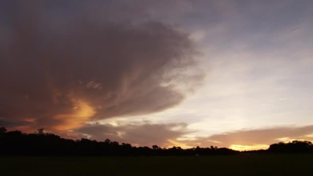 Storm clouds reflect golden light at sunset.