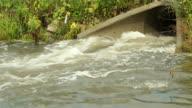 Storm Drain Culvert with Raging Water below Road