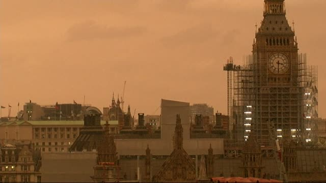 Orange skies over Houses of Parliament rooftop shot ENGLAND London Westminster EXT Houses of Parliament and Westminster skyline at midafternoon with...