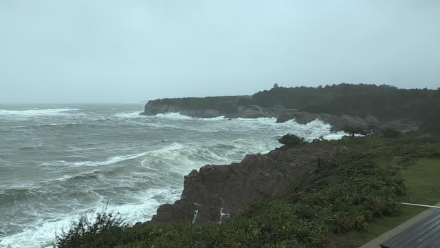 Storm waves crash against the rocky coastline near Jamestown, Rhode Island.