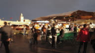 MS T/L Stormy skies over Djemaa el-Fna square and people eating food at stall / Marrakech, Morocco