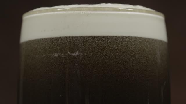 Stout Dunkles Bier in ein pint-Glas Schwenken