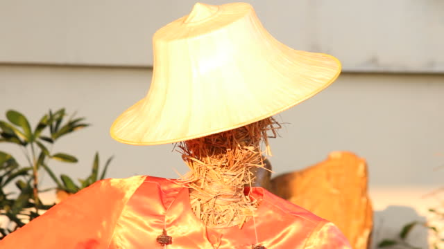 Straw doll with farmer hat stand against wind