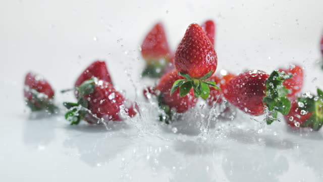 SLO MO LD Strawberries bouncing off water covered surface
