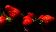 Strawberries Bouncing Off Water Covered Surface