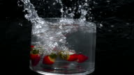 Strawberries fall into a large bowl of fresh water creating a splash as the camera revolves around it in slow motion.