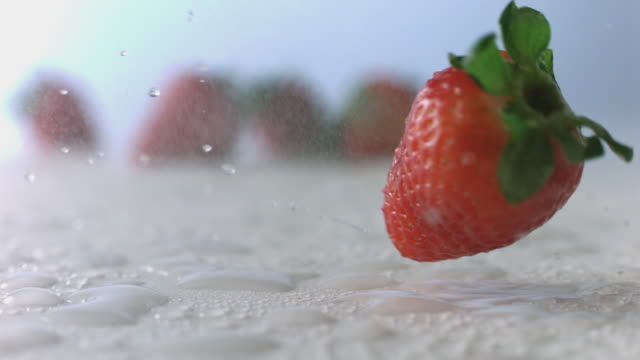 Strawberry tumbles and spins through mist on wet, white surface