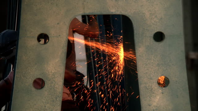 A stream of sparks flies as a steelworker grinds a giant slab of metal. Available in HD.