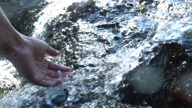 Stream water falling on hand