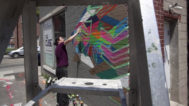 Street artist decorates office wall as camera zooms through ladder timelapse in Toronto Ontario Canada on June 24 2017