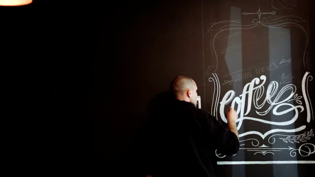 Street artist is doing a chalk graffiti on a black wall in a cafe