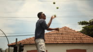 Street Artist juggles four balls at traffic light with covered eyes