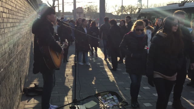 Street artist play the guitar on Feb 11 2017 at famous Houhai Area in Beijing China