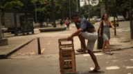 Street Artist stepping on a box and juggles four balls at traffic light with covered eyes