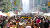 Street Fair was opened on 6th Avenue between 42nd street and 57th street Manhattan New York on Aug. 19 2017. People walk down among the many shopping booths and food venders along the both side of 6th Avenue skyscrapers.