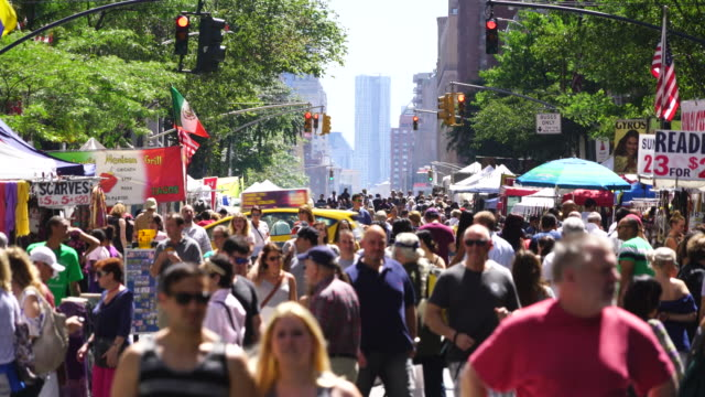 Street Fair was opened on the Lexington Avenue at Midtown Manhattan New York on Jul. 30 2017. Crowd walks down the Lexington Avenue among the many street shops along the tree lined street. Rows of Midtown buildings can be seen behind.