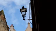 Street lamp in an alleyway with rooftops and chimneys