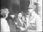Street sign church and statue holding flags in Normandy / Allied Ground Commander British General Bernard Montgomery greets King George VI / King...
