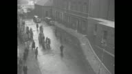 'Downing St' / high angle view of a wet street in front of the Prime Minister Stanley Baldwin's London home / pan of crowd to door of number 10 / VS...