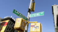 ZI Street signs at the intersection of Lafayette and Spring streets, with upper stories of buildings beyond / New York City, New York, United States