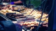 En gata leverantör kockar grillspett av kött på en grill