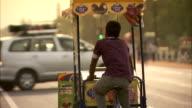 A street vendor pedals his cart along a street in Delhi, India,