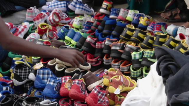 A street vendor selling baby shoes in various colours