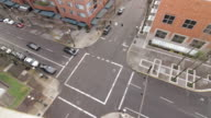 Street view from a rooftop showing cars and cyclists passing through an intersection