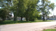 Street w/ trees no cars partially blocked houses behind trees BG OH residential neighborhood
