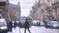 A streetcar passing by the corner thronged with people Medium Long Shot