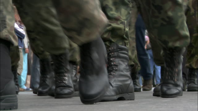 Street-level view of combat boots of soldiers marching in military parade / Krakow, Poland