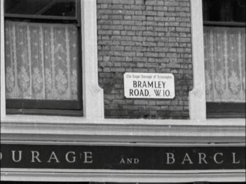 / Streets where race riots occurred / Street sign Bramley Road and pub below / MS People in street 2 police walk along street